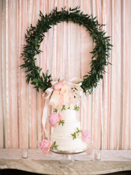 Three-tiered cake with greenery wreath in the background